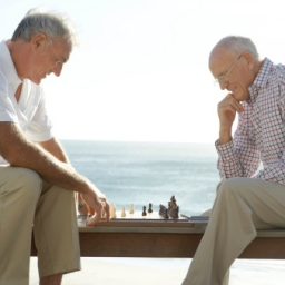Two Senior Men Playing Chess, with the Sea in the Background